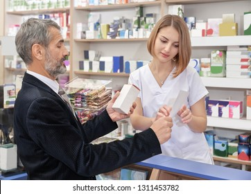 Beautiful woman working in drugstore and helping, consulting clients. Mature man showing prescription, holding medicament in hand. Pharmacist wearing in white lab uniform.