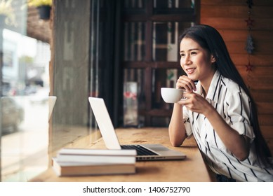 Beautiful woman working with laptop computer at coffee shop cafe