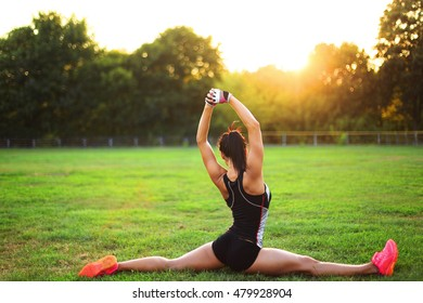 Beautiful woman workout during the morning training on the park. Young sport woman exercising outside at sun background