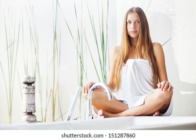 Beautiful woman wrapped with a towel  relaxing in light interior