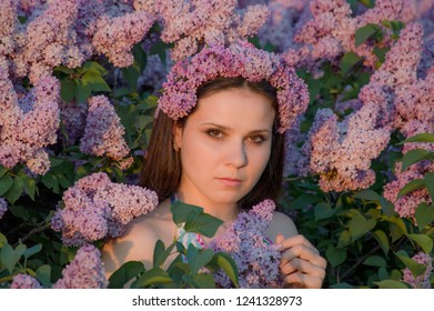 Beautiful woman with a  wreath of lilac. Girl in a wreath of lilac in the spring. Lilac wreath. Lilac. Posing at a photo shoot
