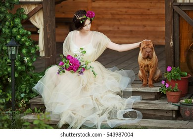 beautiful woman with a wreath of red flowers. woman with a dog in the garden