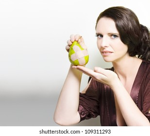 Beautiful woman wrinkling her nose in disgust at an unappetising pear with a bandaid cross in a Bruised fruit or unappealing healthy eating concept