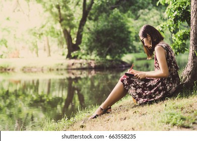 beautiful woman writing into her diary, in the park