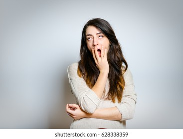 Beautiful woman yawns, bored, isolated on gray background