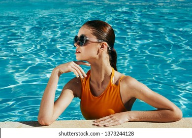 A beautiful woman in a yellow bathing suit with dark glasses is bathed in a swimming pool relaxing holiday