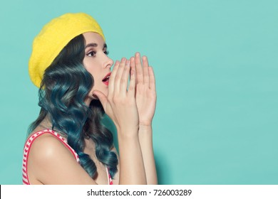Beautiful woman in a yellow beret makes speaker from her hands. On a blue background.
