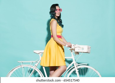 Beautiful woman in yellow dress on white bicycle. On a blue background.
