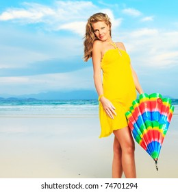 Beautiful woman in yellow dress with umbrella