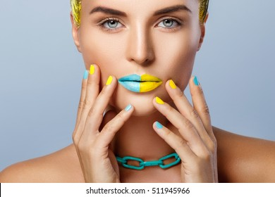 Beautiful woman with yellow hair, colorful manicure and lips covered with two kinds of lipsticks