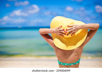 Beautiful woman in yellow hat on white tropical beach