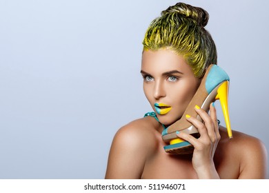Beautiful woman with yellow holding colorful shoes isolated on gray background