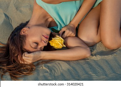 Beautiful woman with a yellow rose lies on the beach