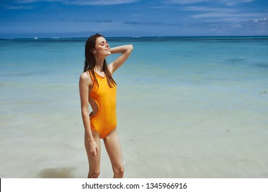 Beautiful woman yellow swimsuit transparent water ocean tourism sea