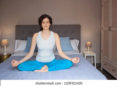 Beautiful woman in yoga position on bed in home bedroom interior at night, meditating with eyes shut. Spiritual activities early morning, indoors. Leisure recreation activities, serene lifestyle.