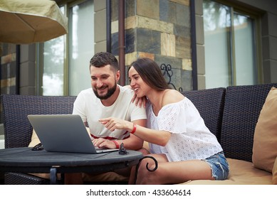 Beautiful woman and young bearded man are sitting and smiling on open terrace in the yard, woman is pointing at something in laptop computer