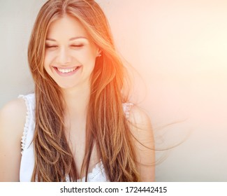 Beautiful woman. Young girl with rays of sunset bill. Portrait.