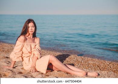 Beautiful woman,posing in boho style beach dress near the sea