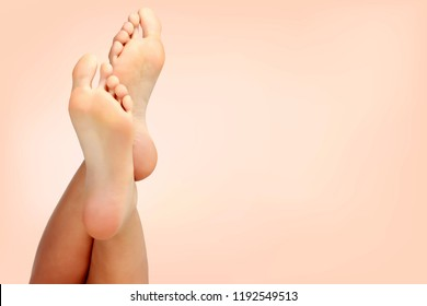 Beautiful woman's bare feet against a pastel background with copyspace