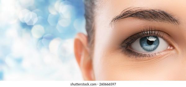 Beautiful woman's blue eye close up looking at camera