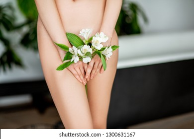 Beautiful woman's body with flower covering her intimate place in the bathroom