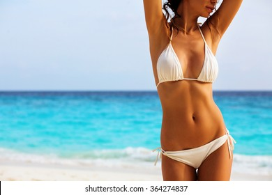 Beautiful woman's body in sexy bikini over beach background