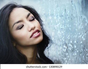 Beautiful woman's face with eyes closed as water surrounds her