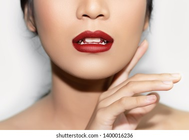 beautiful woman's face From nose to chest Showing bright pink lips And clean, healthy natural skin cleared, there are four canine vampire teeth under the concept of beauty And skin care