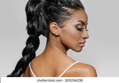 Beautiful woman's face in profile, hair braided; isolated against light grey background.