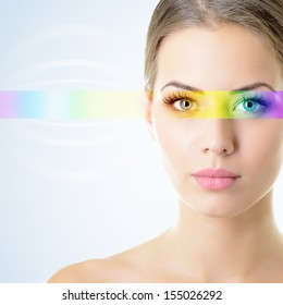 beautiful woman's face with rainbow light on eyes