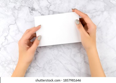 Beautiful womans hand with manicure holding business card. Office work concept.