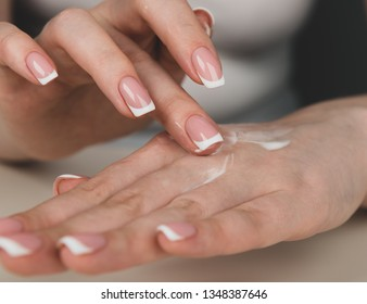 Beautiful woman's hands applying cream