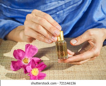 Beautiful womans hands holding a small vial of scented oil. Arab Attar.