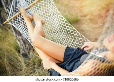 Beautiful woman's legs in hammock. Woman relaxing in hammock in a forest. Selective focus, closeup.