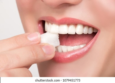 Beautiful woman's mouth with big white teeth bites on a white sugar cube