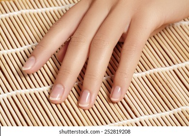 Beautiful woman's nails with perfect french manicure on natural bamboo. Care for female hands