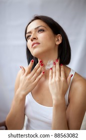 Beautiful women applying moisturizer cosmetic cream on neck.