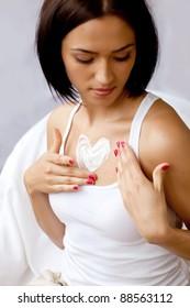 Beautiful women applying moisturizer cosmetic cream.