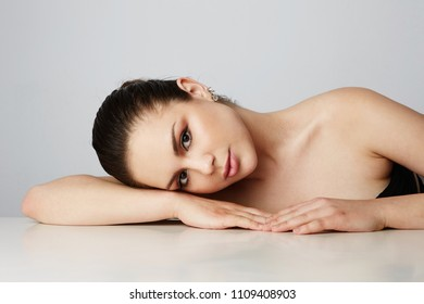 Beautiful women with big brown eyes and dark eyebrows relaxing over empty gray studio background.Model with light nude make-up.Copy paste space,close up.Healthcare skin concept