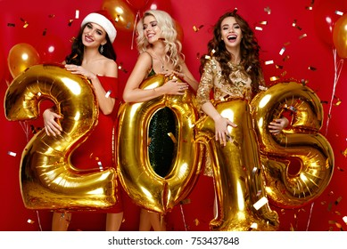 Beautiful Women Celebrating New Year. Happy Gorgeous Girls In Stylish Sexy Party Dresses Holding Gold 2018 Balloons, Having Fun At New Year's Eve Party. Holiday Celebration. High Quality Image