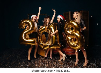 Beautiful Women Celebrating New Year. Happy Gorgeous Girls Holding Gold 2018 Balloons, Having Fun At New Years Eve Party. Holiday Celebration.