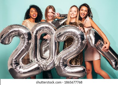 Beautiful Women Celebrating New Year.Happy Gorgeous Female In Stylish Sexy Party Dresses Holding Silver 2021 Balloons, Having Fun At New Year's Eve Party. Holiday Celebration.Charming Models