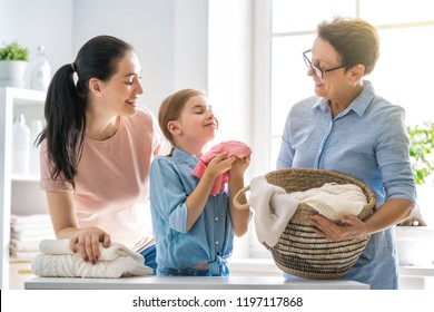 Beautiful women and child girl little helper are having fun and smiling while doing laundry at home.