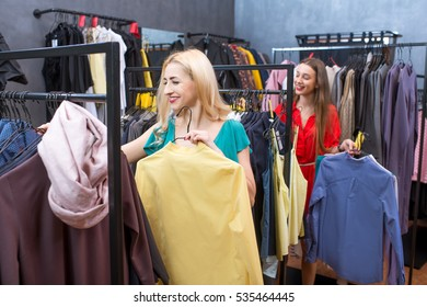 Beautiful women choosing garments in the clothing store. Female friends having fun shopping in the boutique