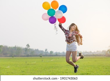 Beautiful women with colorful balloons happily jumping in the lawn at sunset.