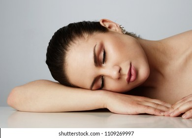 Beautiful women with dark eyebrows sleeping with over empty gray studio background.Model with light nude make-up.Copy paste text space,close up.Healthcare skin makeup concept