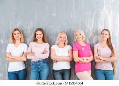 Beautiful women of different ages with pink ribbons on grey background. Breast cancer concept