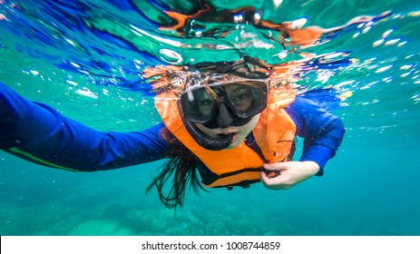 Beautiful women are diving snorkeling in the sea.