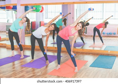 Beautiful women doing fitness exercise with weight in hands. Active and healthy lifestyle will give you a flat stomach, firmer breasts and sexy body