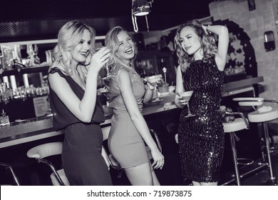 Beautiful women drink cocktails and dance in the bar.